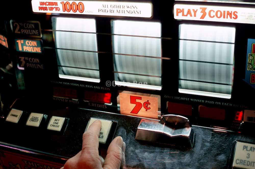 finger pushing button on slot machine