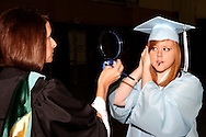 Julie Sterner (left) holds a mirror for Caitlin Sprouse before the Fairborn High School commencement at the Nutter Center in Fairborn, Friday, May 27, 2010.