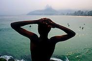 Rio de Janeiro, Brazil.<br /> A boy looks out over the ocean at Ipenema beach.