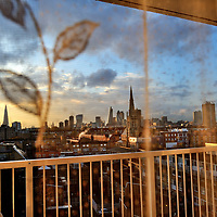 View west to the City of London through the net curtains of a flat in a high rise housing block in-between Shadwell and Limehouse in the East End. The Shard stands to the left.
