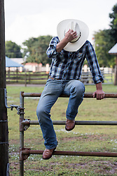 cowboy holding his hat while seated on a metal gate at a ranch