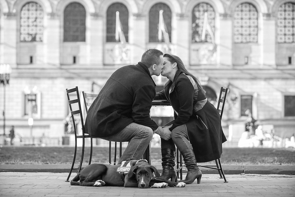 A kiss with Liberty, their dog, in front of the Boston Public library.