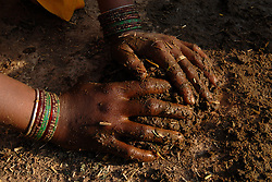 Chitrakoot District, Uttar Pradesh, India: Woman create dung patties  using a mixture of cow dung and straw. In India, dung patties are used for fuel in heating homes and cooking food. Dung is renewable energy source and relatively inexpensive.  (Photo by Ami Vitale)