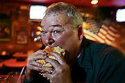 "Carson 'Collard Green"" Hughes, devours giant hamburger at a bar in Newport News, Virginia.  He died in December 2008, at age 44. (From the book What I Eat: Around the World in 80 Diets.)  MODEL RELEASED."
