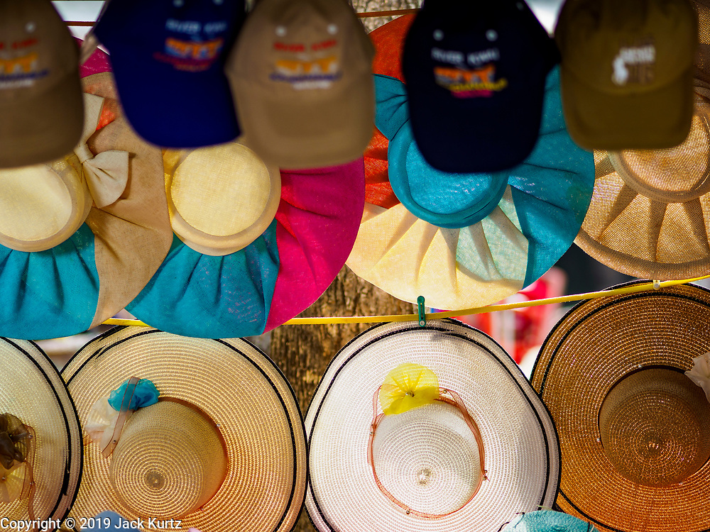 """09 JANUARY 2019 - KANCHANABURI, THAILAND: Tourist hats for sale at the """"Bridge On the River Kwai"""" in Kanchanaburi. Hundreds of thousands of Asian slave laborers and Allied prisoners of war died in World War II constructing the """"Death Railway"""" between Bangkok and Rangoon (now Yangon), Burma (now Myanmar) for the Japanese during World War II.  The bridge is now one of the most famous tourist attractions in Thailand.      PHOTO BY JACK KURTZ"""