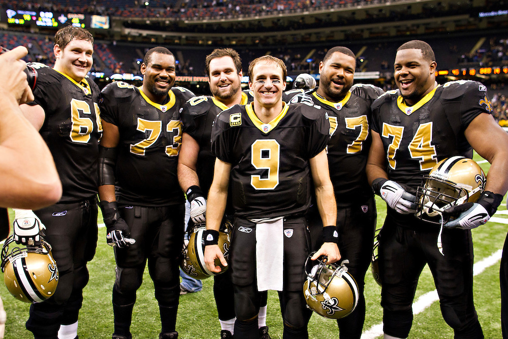 NEW ORLEANS, LA - DECEMBER 26:   Quarterback Drew Brees #9 and the offensive line of the New Orleans Saints pose after the game for a photo after Brees throws a nine-yard touchdown pass to running back Darren Sproles #43 and breaks the single-season passing record in the fourth quarter against the Atlanta Falcons at Mercedes-Benz Superdome on December 26, 2011 in New Orleans, Louisiana.  The Saints defeated the Falcons 45-16.  (Photo by Wesley Hitt/Getty Images) *** Local Caption *** Drew Brees