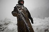 A Pakistani soldier is seen at a checkpoint as a blizzard arrives in the ski resort of Malam Jaba, on 25 February, 2011, in the Swat Valley, Pakistan. The resort was blown up by the Taliban after they had finished using it as a base of operations during the recent conflict in the Swat Valley.