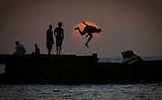 A local lad dives off a pier at sunset near Bridgetown, Barbados. (2008)