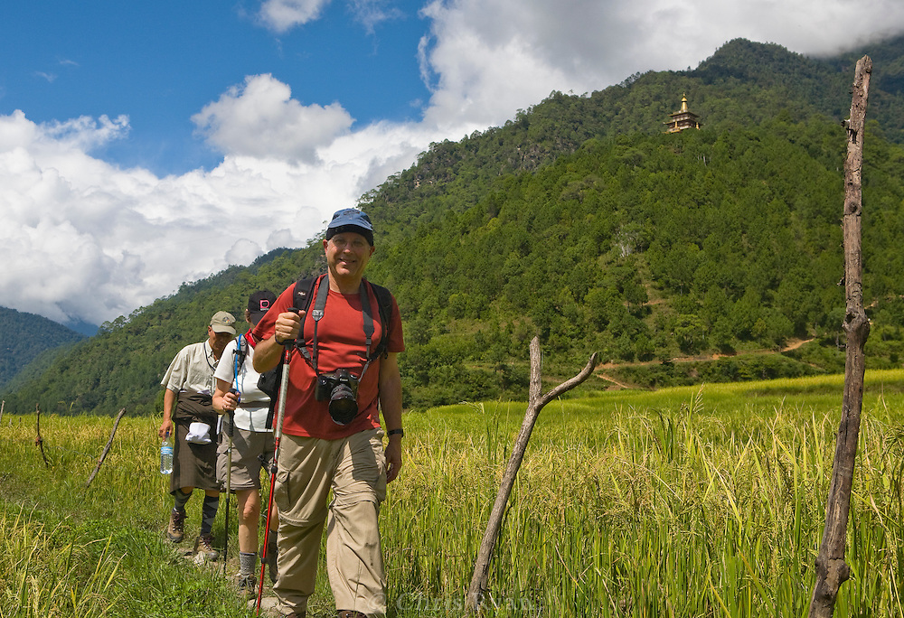 Hikers in Punakha Valley, Bhutan (background: Khamsum Yuley Namgay Chorten)