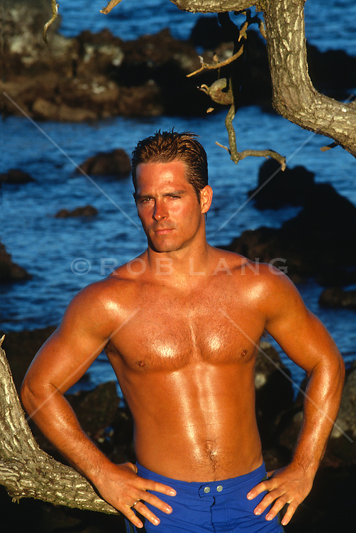 Tan shirtless man standing in golden sunlight with  hands on his hips