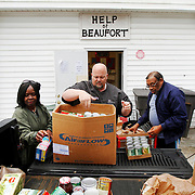 "Mike Covert, president and owner of Covert Aire, center, unloads 2,500 pounds of food with the help of Rose Marie Speaks, of Beaufort, volunteer, left, and Paul Graham, vice chairman of the board at Help of Beaufort, right, at HELP of Beaufort on December 31, 2013.   Steve Curless, president of Help of Beaufort, not pictured, said ""the donations will provide about 250 people with food.  This donation came at a good time because it will help stock out shelves for the drier times that are common in January -  when donations begin to wane."""