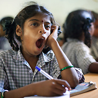 Viyashree Viswanathan in her 5th Standard class at the Thalanuda Government School. Vijyashree's grades have been falling in recent months. The benches on which Vijyashree and her fellow students work were supplied by Unicef following the tsunami.<br />