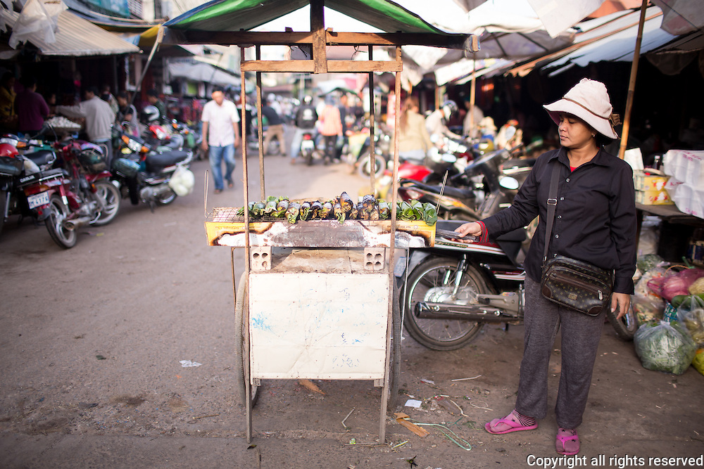 Street food vendor grills glutinous rice wrapped in banana leaf in a market in Siem Reap, Cambodia