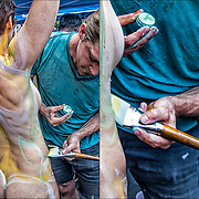 Artist painting models body.<br /> <br /> Body painting can be viewed as a  form of public performance art.<br /> <br /> In Washington Square Park gives models the opportunity to embrace themselves and to use their bodies to become living art. Unlike what people might expect from a body painting event, the models are ordinary people, ranging in age, size and gender. Models take great pride standing in public as they are. By holding the event as a full nude event, we remove the shame often associated with our bodies and show the distinction between nudity and sexuality.<br /> <br /> The public gets to see all types of bodies, which is especially important since the perception of the human form is twisted by advertising and the media, which is the source of anxiety for so many of us. <br /> <br /> Body Painting celebrates the unique art form and promotes artistic expression, body acceptance and human connection through art - It&rsquo;s about artistic expression of many artists all at once, each with their own unique approach.