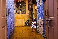 Informal portrait of a little girl in the family courtyard house with blue walls. Indian people and culture. Fine art photography prints for sale. Exotic people and places wall art