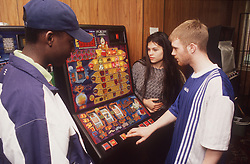 Group of teenagers playing fruit machine in games arcade,