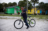 "Claudius Taylor III, 6, pauses from a bike ride on his family's property to pose for a photo Jan. 12, 2016, in East Stuart. Claudius' father, Claudius ""Lucky"" Taylor Jr., took over managing the rental properties and grocery store, which his parents opened in 1972. (XAVIER MASCAREÑAS/TREASURE COAST NEWSPAPERS)"