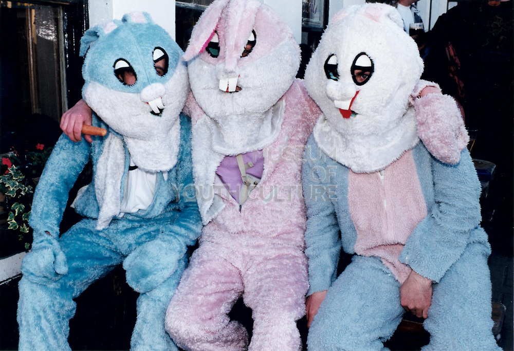 Three young people in rabbit costumes sitting together posing.