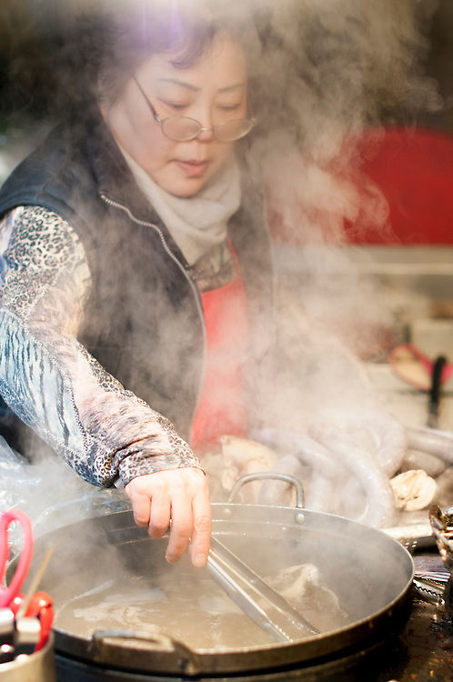 A pojangmacha proprietor cooks sundae, a type of sausage, at a food stall in Seomyeon. Busan, South Korea.