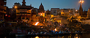 Tourists watch body bathed in River Ganges and Hindu funeral pyre cremation, Manikarnika Ghat in Holy City of Varanasi, India
