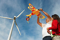 Father holding airplane kite with daughter (7-9) at wind farm