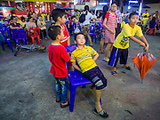 "06 DECEMBER 2015 - BANGKOK, THAILAND: Children watch a Chinese opera performance at the Ruby Goddess Shrine in the Dusit district of Bangkok. Chinese opera was once very popular in Thailand, where it is called ""Ngiew."" It is usually performed in the Teochew language. Millions of Chinese emigrated to Thailand (then Siam) in the 18th and 19th centuries and brought their culture with them. Recently the popularity of ngiew has faded as people turn to performances of opera on DVD or movies. There are about 30 Chinese opera troupes left in Bangkok and its environs. They are especially busy during Chinese New Year and Chinese holidays when they travel from Chinese temple to Chinese temple performing on stages they put up in streets near the temple, sometimes sleeping on hammocks they sling under their stage.     PHOTO BY JACK KURTZ"