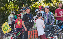 © Licensed to London News Pictures. 14/09/2019. Felton, North Somerset, UK. Police speak to cyclists who had circled the roundabout outside the entrance to Bristol Airport for an Extinction Rebellion protest against the proposed expansion plans for Bristol Airport. The campaigners say that there will be more air pollution from increased flights which are not counted in the airport's target to be carbon neutral by 2025, that there will be a loss of greenbelt land, more noise pollution from more flying, traffic congestion, and ill health from respiratory and cardiac disease. Campaigners say a recent report found that the incidence of asthma and respiratory diseases was on average 17% higher among those living within 6.2 miles of a major airport and that cardiac diseases were 9% more common. Photo credit: Simon Chapman/LNP.