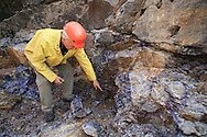 Steve Lukinuk, president of Amethyst Mine Panorama, points to rich vein of amethyst in his open-pit mine, largest deposit in Canada; Dorion, Ontario.