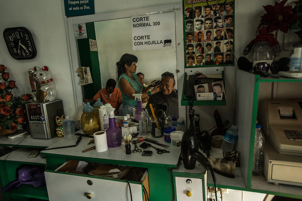"MARACAY, VENEZUELA - MARCH 21, 2016:  A stylists gives a man a buzz cut at a military barbershop in Maracay, where residents and businesses are regularly subject to  state-mandated electricity rationing.  The owner of the barbershop bought a generator so that the business can continue operating when their electricity is shut off.  Venezuela is shutting down this week, as the government struggles with a deepening electricity crisis.  President Nicolas Maduro gave everyone an extra three days off work, extending the two-day Easter holiday, according to a statement in the Official Gazette published late last Tuesday.  The government has rationed electricity and water supplies across the country for months and urged citizens to avoid waste as Venezuela endures a prolonged drought that has slashed output at hydroelectric dams. The ruling socialists have blamed the shortage on the El Nino weather phenomena and ""sabotage"" by their political foes, while critics cite a lack of maintenance and poor planning.  PHOTO: Meridith Kohut for Bloomberg News"