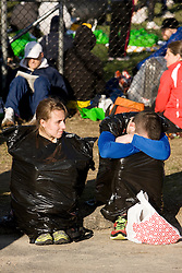 runners stay warm in garbage bags and wait in village prior to race
