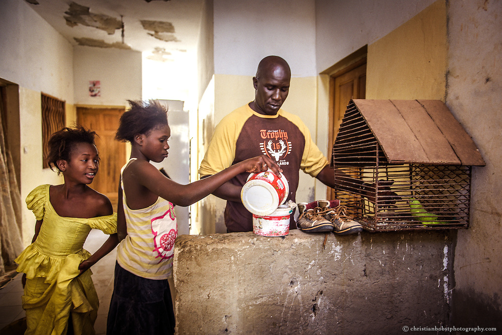 Lac de Guiers feeds his parrot at his home in Dakar on April 4, 2015. The former fighter now leads a peaceful life with his wife, his daughters. He has an income with his wrestling school.