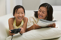 Mother and Daughter Playing Video Game and Reading on Couch