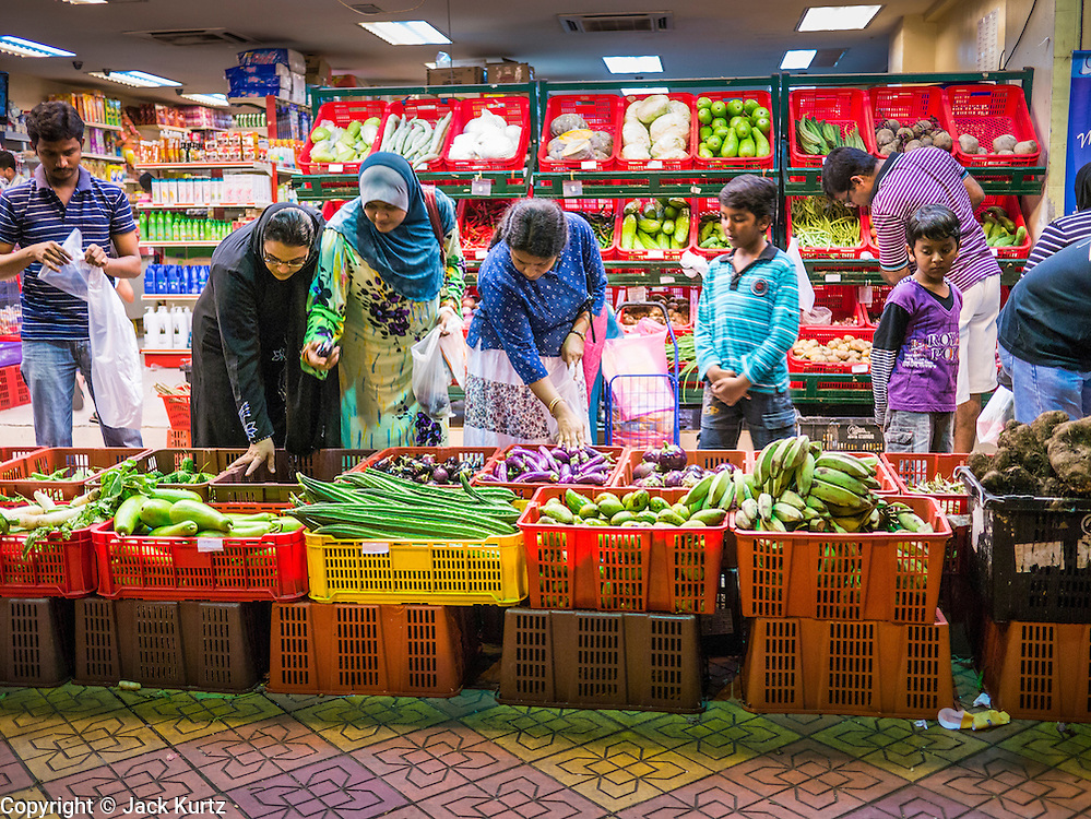 """20 DECEMBER 2012 - KUALA LUMPUR, MALAYSIA:  People shop for fresh vegetables at a market on Jalan Tun Sambanthan, the main street in """"Brickfields,"""" the Little India section of Kuala Lumpur, Malaysia. The """"Little India"""" section of Kuala Lumpur is also known as """"Brickfields."""" The area has recently been renovated and has emerged as a tourist draw. It's within walking distance of KL Stesen Sentral, the Kuala Lumpur central train station.    PHOTO BY JACK KURTZ"""