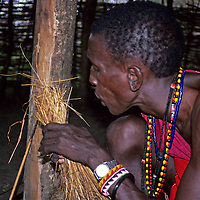 Africa, Kenya. Maasai tribesman demonstrates starting fire