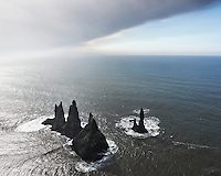 Reynisdrangar Sea Stack seen from above from Reynisfjall mountain. Ashcloud above from Volcano Eyjafjallajökull. South Shore Iceland.