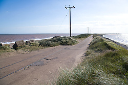 Road next to eroded railway line at Spurn Head; East Yorkshire; England; with North Sea on the left and Humber Estuary on the right,