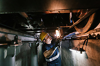 GIOIA TAURO, ITALY - 13 JUNE 2018: A worker checks a locomotive under maintenance here at Gruppo Ventura,  a family-owned company that installs railroad tracks and does locomotives maintenance,  in Gioia Tauro, Italy, on June 13th 2018.<br /> <br /> Alessandro Ventura, CFO of Gruppo Ventura, traveled there some 20 times over the last three years, establishing a venture with an Iranian company engaged in expanding the national rail network. In March 2017, he signed a 2 million euro contract (about $2.3 million) to service a section of rail outside Teheran.<br /> He shipped two locomotives used to tamp down the rocks below railroad tracks. They went out on a freighter from Gioia Tauro, a port on the Tyrrhenian Sea that has long been notorious as a Mafia-run conduit for cocaine trafficking.<br /> Last August, Mr. Ventura stood at the Iranian port of Bandar Abbas in 122 degree heat, watching a crane hoist the locomotives onto the docks.<br /> Now, those machines are effectively marooned, the business halted. Gruppo Ventura has lost appetite for adventurous expansion.<br /> <br /> Once the Obama administration struck the nuclear deal with Iran three years ago, Italy saw a chance. Last year, Italy exported more than 1.7 billion euros (nearly $2 billion) worth of goods to Iran. Then, President Trump withdrew the United States from the Iran deal and vowed to reinstate sanctions, dealing a blow to companies across Europe — especially those from Italy, Germany and France.