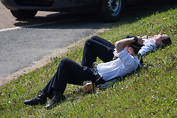 London, UK. 19th April, 2019. Police officers relax on the grass alongside the main motorway approach to Heathrow airport following a small protest earlier by Extinction Rebellion Youth. A large policing operation was put in place in and around the airport in preparation for expected protests by climate change activists from Extinction Rebellion. Only a very small symbolic protest by teenage activists from Extinction Rebellion Youth took place, dispersed by police officers under threat of arrest.