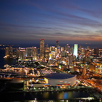 Aerial of downtown Miami, Florida at twilight with city lights glowing.  Featuring American Airlines Arena in the foreground.