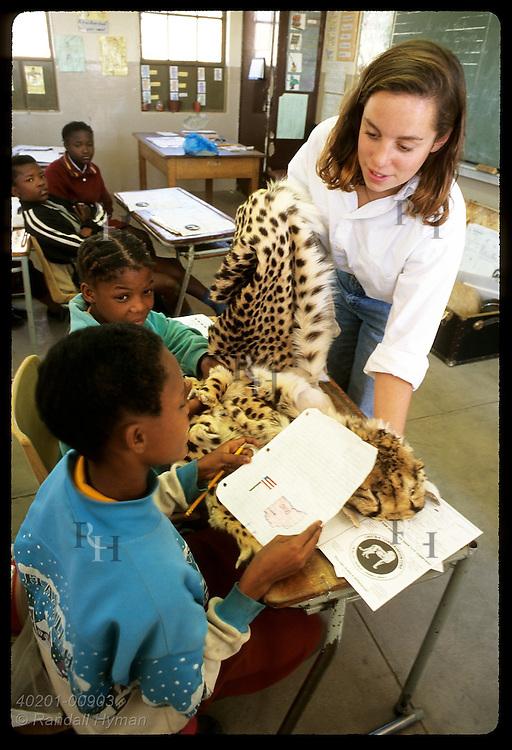 CCF volunteer Kim Benedict shows two 12-yr-old girls cheetah pelt at Rogate School;(v) Otjiwarongo Namibia