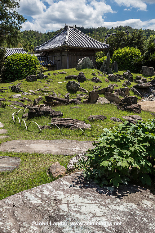 Awa Kokubunji Tokushima - is a nationally designated scenic spot plus it is the 15th stop along the Shikoku Buddhist Pilgrimage trail. Besides all this, Awa Kokubunji has a very unique and powerful garden in which scenic spots from China are represented.. Awa Kokubun-ji is one of the most dynamic examples of the traditional dry landscape gardens developed in Japan, a style known as karesansui. The original garden was laid out 5 centuries ago during the Momoyama period.  Elaborate rock arrangements were added more recently, around 200 years ago. This has created the garden as it is seen today. The audacious, unconventional arrangements of large rocks are believed to have been a significant inspiration for the world renowned sculptor Noguchi Isamu who lived nearby.  The official name of the temple is Yaku Ozan Konjiki-in Kokubunji.