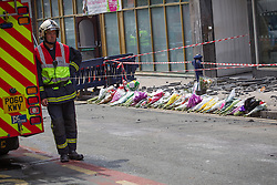 © Licensed to London News Pictures . FILE PICTURE DATED 15/07/2013 . Oldham Street , Manchester , UK . A fireman leans against a fire truck alongside flowers , tributes and a uniform left at the scene , in front of Paul's Hair World . The scene on Oldham Street following a fire at Paul 's Hair World on 13th July which claimed the life of fireman Stephen Hunt . Photo credit : Joel Goodman/LNP