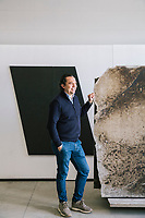 "CHIARAMONTE GULFI (RAGUSA), ITALY - 19 MARCH 2019: Biagio Amarù, CEO of Artigianato Industriale - which produces the Pietra Pece - poses for a portrait next to a Pietra Pece in the Artigianto Industrialre manufacturing plant in Chiaramonte Gulfi (Ragusa), Italy, on March 19th 2019.<br /> <br /> The pietra pece (pitchstone) is a type of limestone which is charachterized by different percentages of bitumen.<br /> This morphologic origin makes the pietra pece particularly unique for its peculiar chromatic shading.<br /> In fact, the pietra pece is also called ""asphaltic stone"" because it has a colour that varies from gray to dark brown.    <br /> The company DESCAT has been the owner of the registered trademark of the pietra pece since 2014 and it has the ownership of the only extractive pietra pece quarry situated in the Tabuna/Cortolillo district in Ragusa, Sicily. The pietra is distributed by Artigianato Industriale."