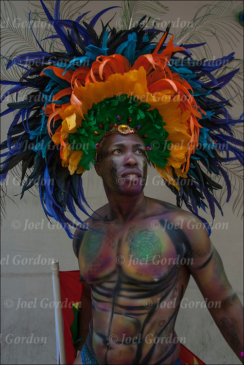 Person of color from Caribbean wearing colorful rainbow pride feathers headdress showing both his Carnival ethnic and gender pride during the Gay Pride Parade 2014 in New York City.