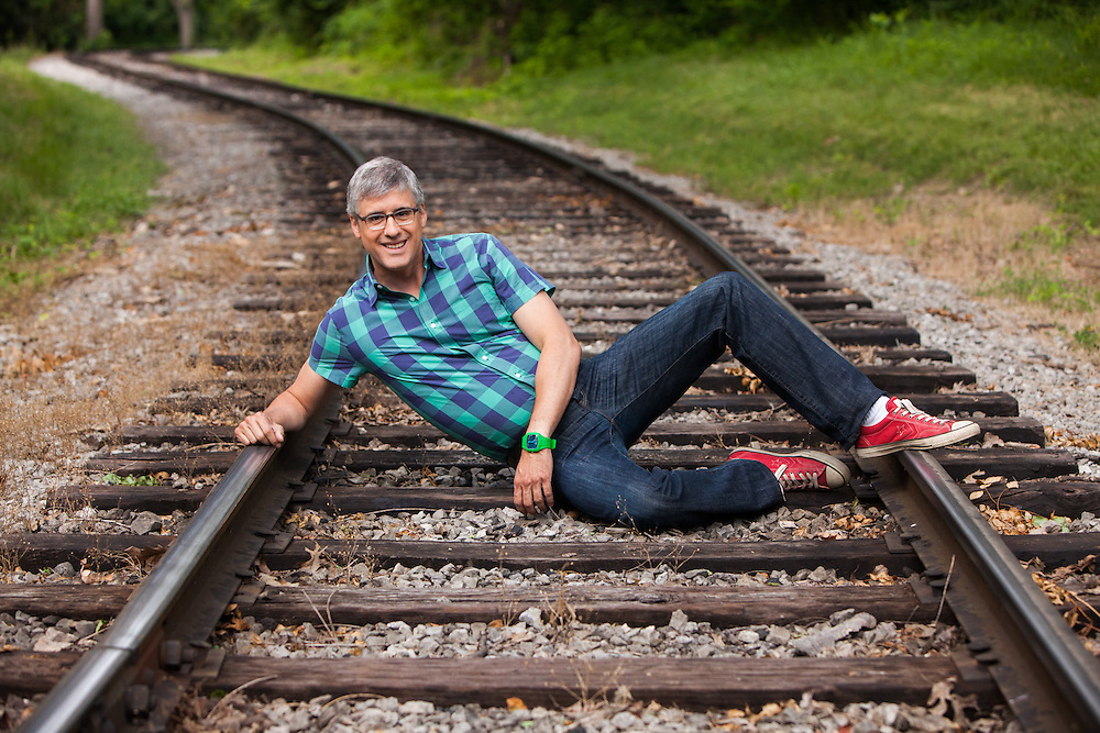 Mo Rocca poses on train tracks while filming CBS Saturday morning's The Henry Ford's Innovation Nation at Greenfield Village. Photographed by set photographer Kristina Sikora