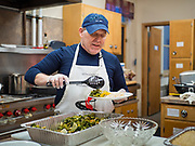 """26 FEBRUARY 2020 - FARMINGTON, MINNESOTA: SCOTT EVENSON, a former professional chef, prepares the meal for the community dinner at Faith Church, a United Methodist Church in Farmington, MN, about 30 minutes south of the Twin Cities. The dinner is sponsored by Loaves & Fishes, a Christian organization that provides food for community dinners and foodbanks. Farmington, with a population of 21,000, is a farming community that has become a Twin Cities suburb. The city lost its only grocery store, a Family Fresh Market, in December, 2019. The closing turned the town into a """"food desert."""" In January, Faith Church started serving the weekly meals as a response to the store's closing. About 125 people per week attend the meal at the church, which is just a few blocks from the closed grocery store. The USDA defines food deserts as having at least 33% or 500 people of a census tract's population in an urban area living 1 mile from a large grocery store or supermarket. Grocery chains Hy-Vee and Aldi both own land in Farmington but they have not said when they plan to build or open stores in the town.      PHOTO BY JACK KURTZ"""