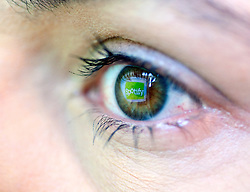 Detail of music streaming website logo reflected in woman's eye
