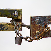 A lock and chain ties two sections of a barricade fence together.
