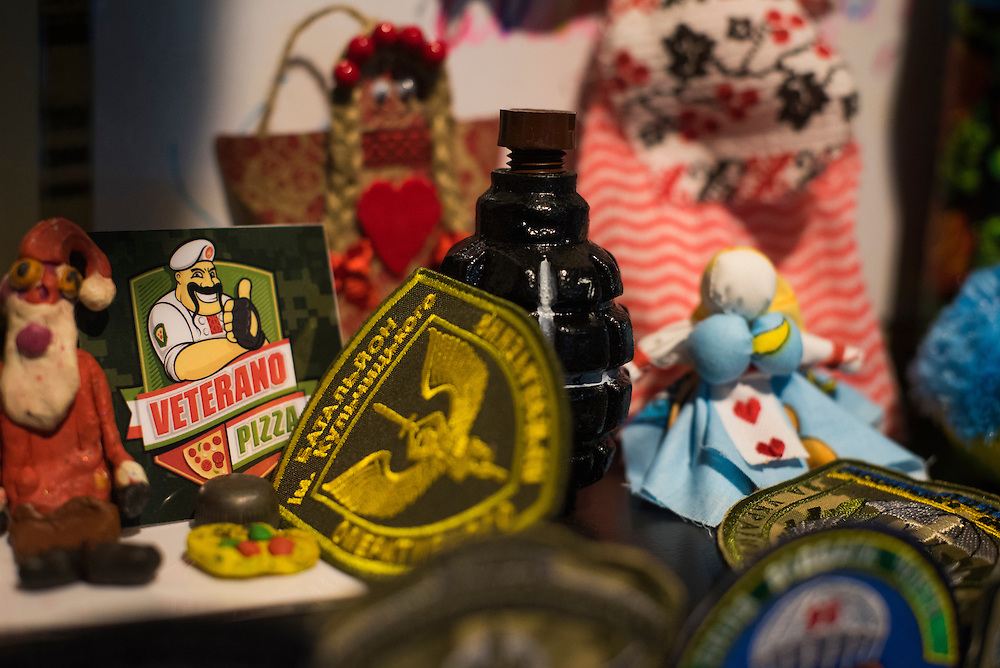 A grenade is seen on a shelf displaying insignias, motanki (a type of Ukrainian doll) and other ephemera at Veterano Pizza on January 23, 2016 in Kiev, Ukraine. (Pete Kiehart for The New York Times)