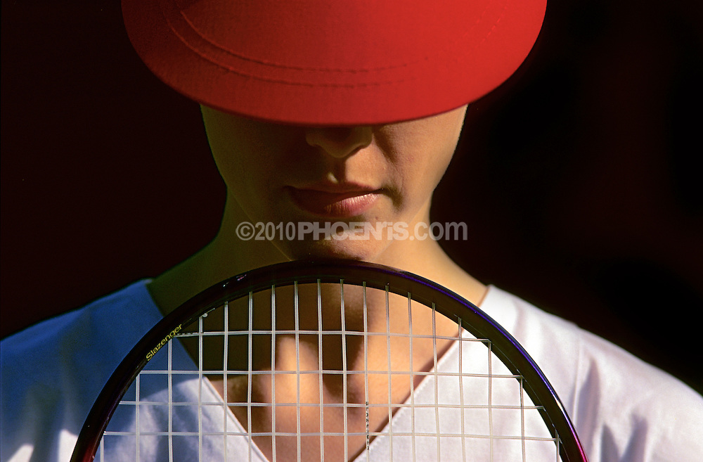 Young female holds tennis racket SPORT